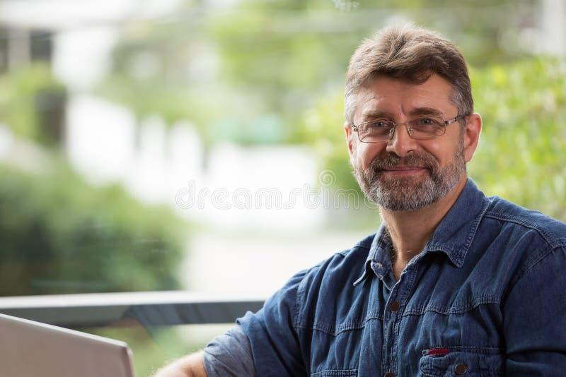Il ritratto dell'uomo anziano sorridente sta sorridendo fotografia stock