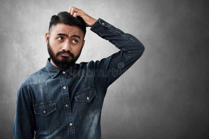 Il ritratto dell'uomo barbuto bello ha confuso fotografia stock