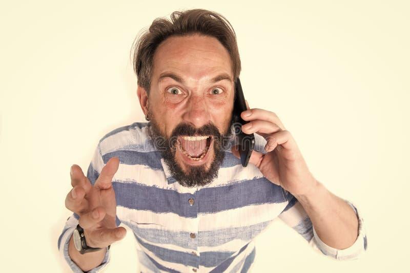 Il ritratto dell'uomo barbuto maturo furioso si è vestito in camicia con le linee blu al telefono cellulare isolato su fondo bian fotografia stock