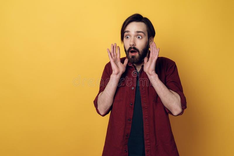 Il ritratto dell'uomo barbuto Shocked tiene le mani su fotografia stock libera da diritti