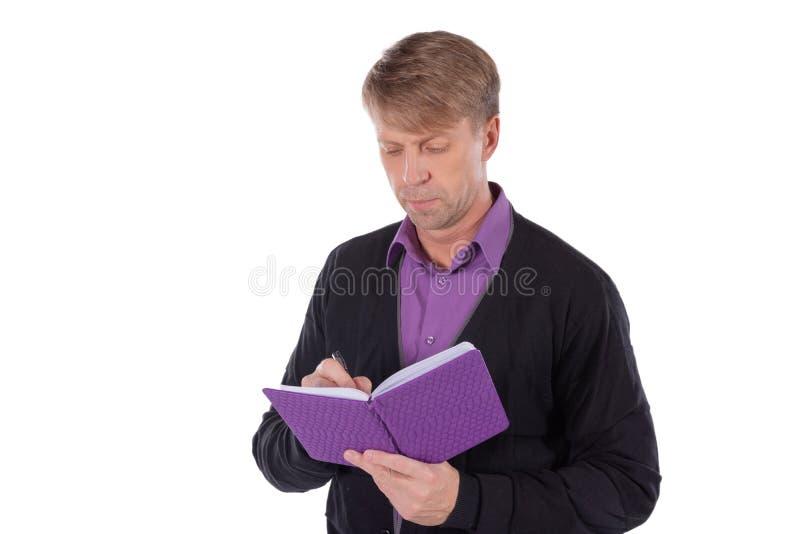 Il ritratto dell'uomo di medio evo vestito in cardigan scrive in un taccuino su fondo bianco immagine stock libera da diritti