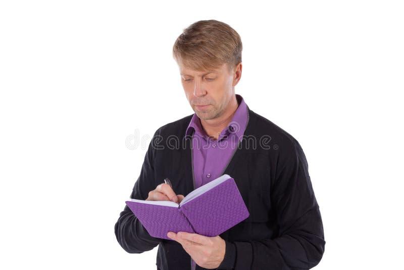 Il ritratto dell'uomo di medio evo vestito in cardigan scrive in un taccuino su fondo bianco fotografia stock libera da diritti