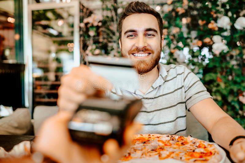 Il ritratto dell'uomo felice che paga il pranzo con la carta di credito, si chiude sui dettagli fotografia stock libera da diritti