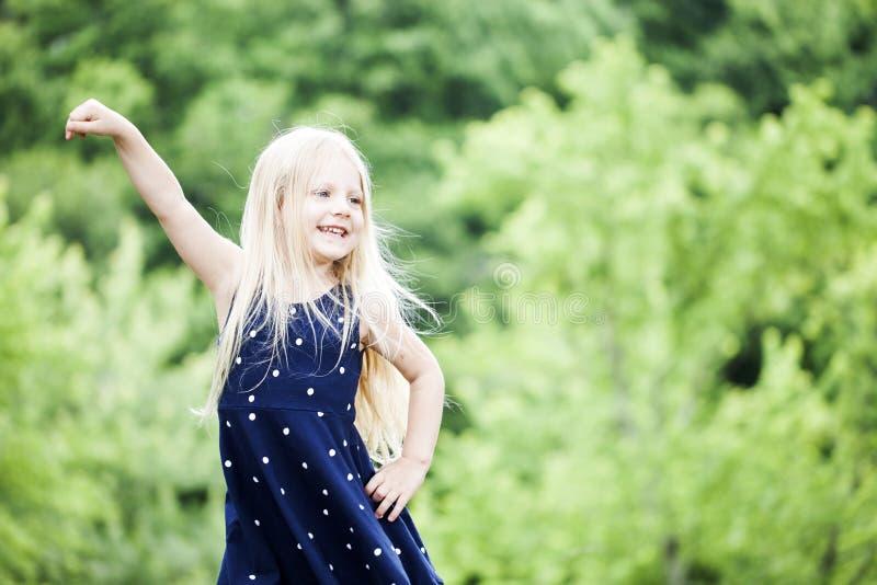 Il ritratto della bambina felice che posa nel blu ha punteggiato il vestito fotografie stock libere da diritti