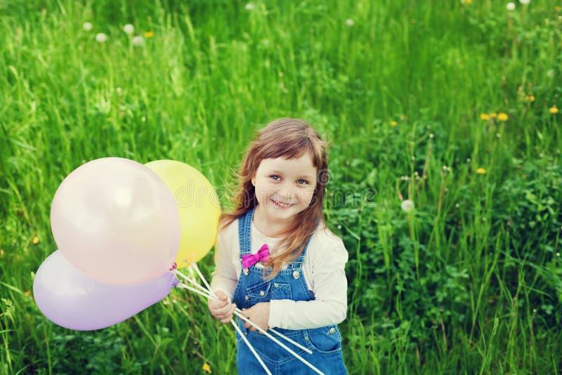 Il ritratto della bambina sveglia con il bello giocattolo della tenuta di sorriso balloons a disposizione sul prato del fiore, in immagine stock libera da diritti