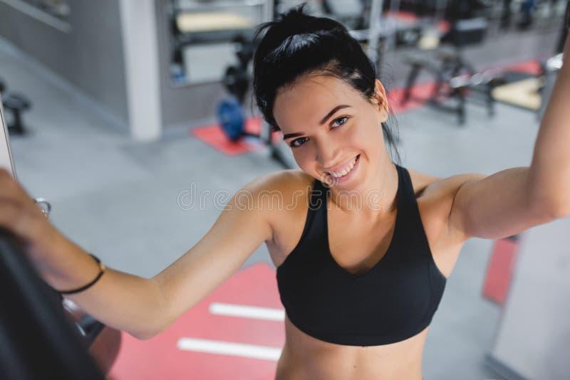 Il ritratto della donna castana di bello sorriso caucasico sta facendo gli esercizi con la barra nella palestra, donna sportiva c immagini stock