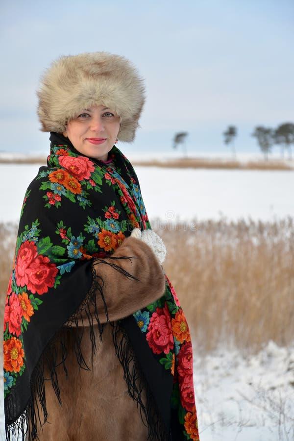 Il ritratto della donna del medio evo in un cappuccio della pelliccia ed in uno scialle variopinto costa contro il lago dell'inve immagini stock libere da diritti