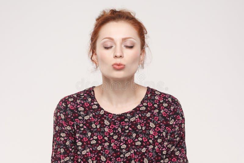 Il ritratto della donna dello zenzero, occhi chiusi ed invia l'aria baciante alla camma fotografia stock