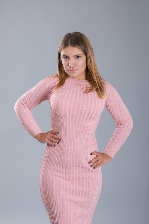 Il ritratto della donna di poca crescita o modello basso si è vestito in vestito rosa tricottato figura non standard immagine stock