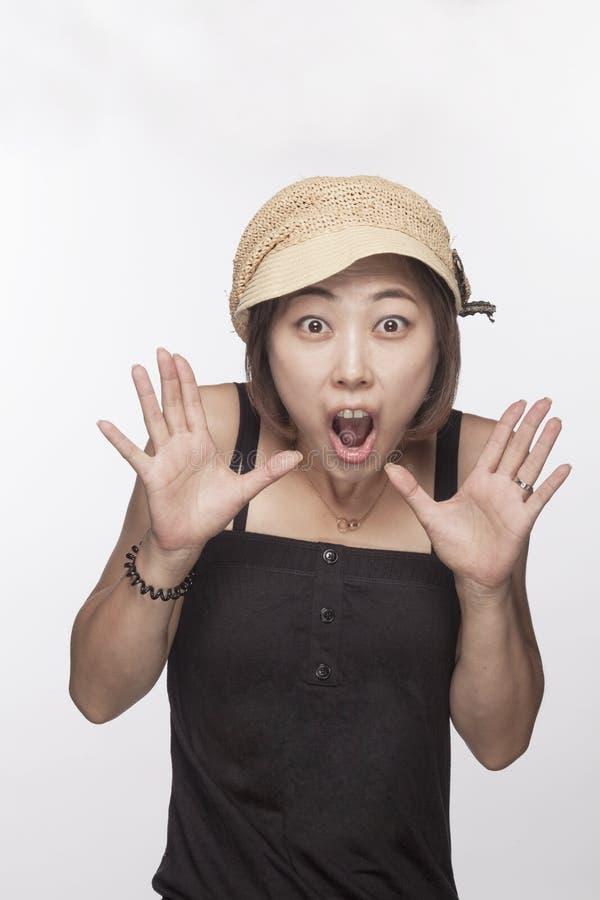 Il ritratto della donna sorpresa con le mani si è alzato, colpo dello studio fotografia stock
