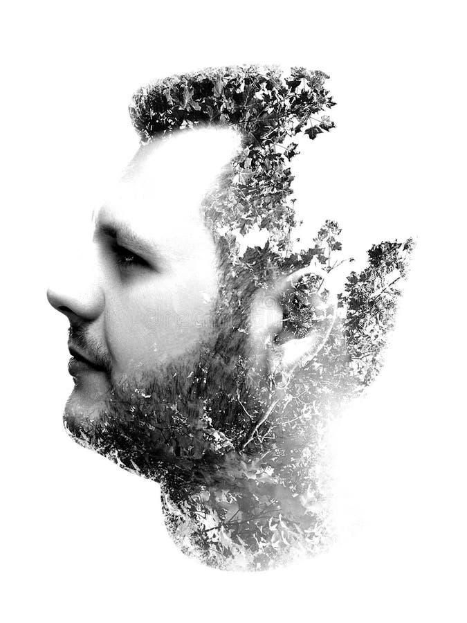 Il ritratto della doppia esposizione dell'uomo si è combinato con i rami e gli alberi immagini stock