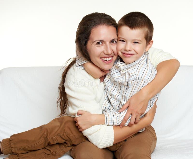 Il ritratto della famiglia del bambino e della madre su fondo bianco, gente felice si siede sul sofà fotografie stock libere da diritti