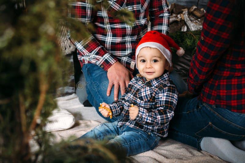 Il ritratto della famiglia di Natale di giovane sorridere felice parents il gioco con il bambino piccolo in cappello rosso di San fotografie stock
