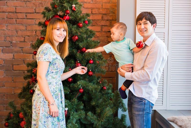 Il ritratto della famiglia di Natale nel salone domestico di festa, Camera che decora dall'albero di natale esamina in controluce immagine stock