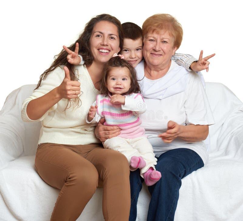 Il ritratto della famiglia su fondo bianco, gente felice si siede sul sofà Bambini con la madre e la nonna immagine stock libera da diritti