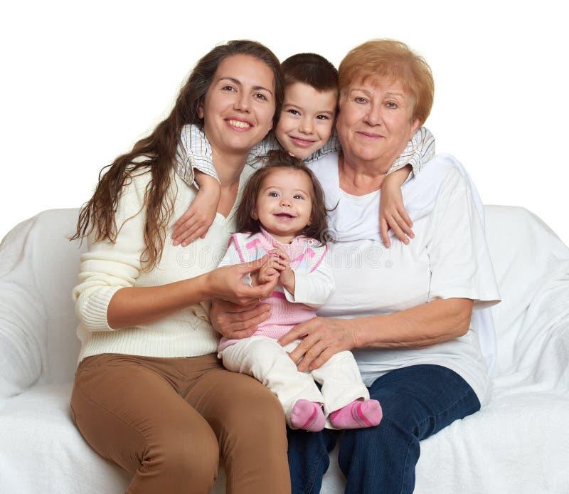 Il ritratto della famiglia su fondo bianco, gente felice si siede sul sofà Bambini con la madre e la nonna fotografia stock libera da diritti