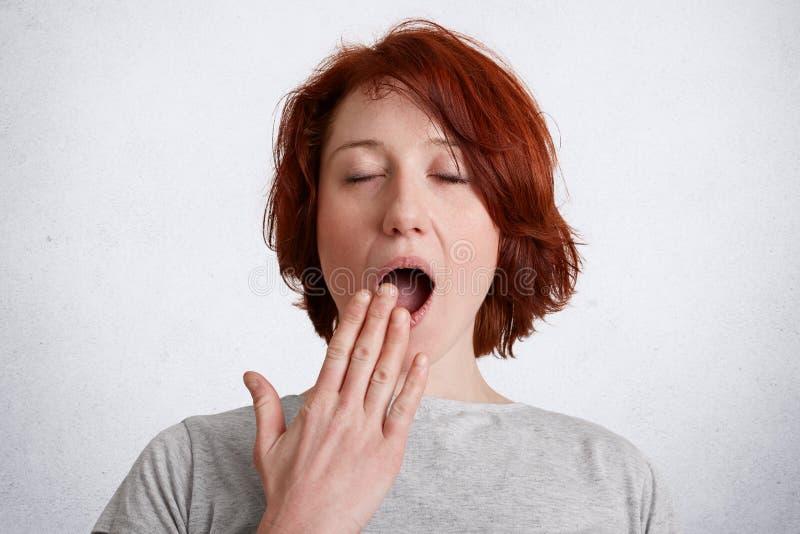 Il ritratto della femmina freckled con i capelli di scarsità rossi, sbadigli, ha espressione sonnolenta, bocca delle coperture co fotografia stock