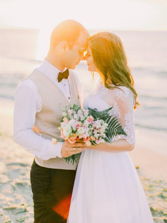 Il ritratto della fine-parte superiore delle persone appena sposate che si tengono per mano ai precedenti del tramonto immagini stock libere da diritti