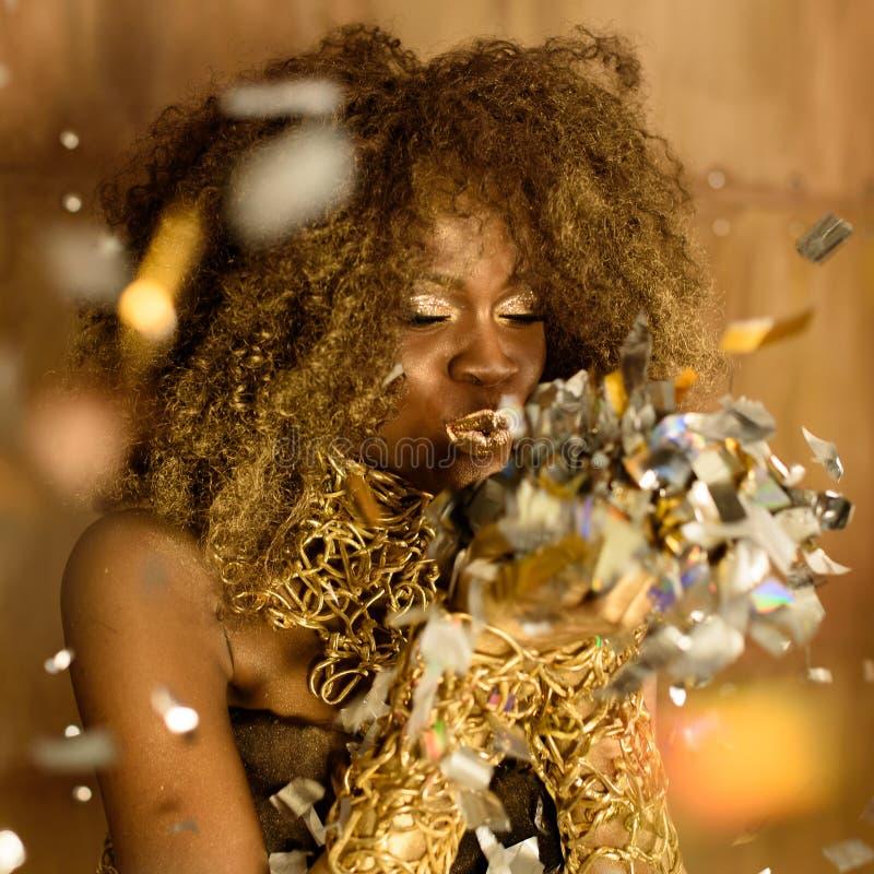 Il ritratto della giovane donna adorabile sveglia che soffia sul piccolo scintillare stars sopra il fondo dell'oro immagine stock libera da diritti