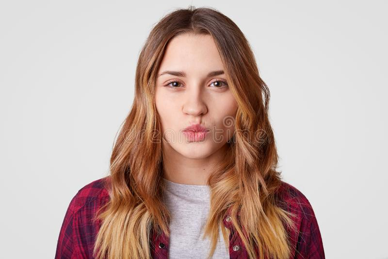 Il ritratto della giovane donna con pelle sana, tiene le labbra arrotondate, vuole baciare il ragazzo, ha capelli ondulati lunghi fotografia stock