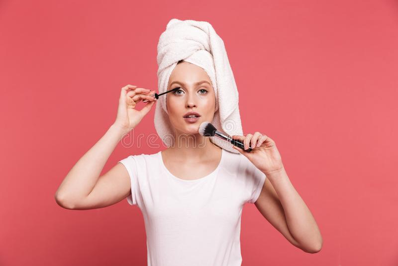 Il ritratto della giovane donna contenta 20s si ? avvolto in asciugamano bianco dopo la doccia che applica i cosmetici con la spa immagini stock libere da diritti