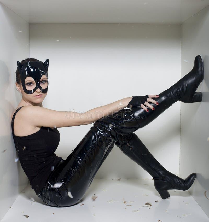 Il ritratto della giovane donna di bellezza nella maschera gradisce il gatto in scatola bianca immagine stock
