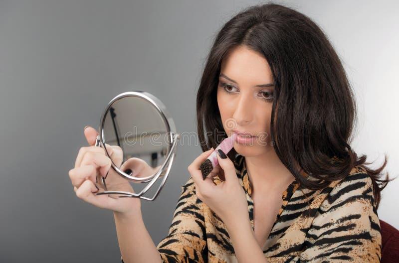 Il ritratto della donna fa le labbra nello specchio immagine stock libera da diritti