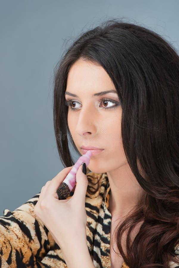 Il ritratto della donna fa le labbra nello specchio immagini stock libere da diritti