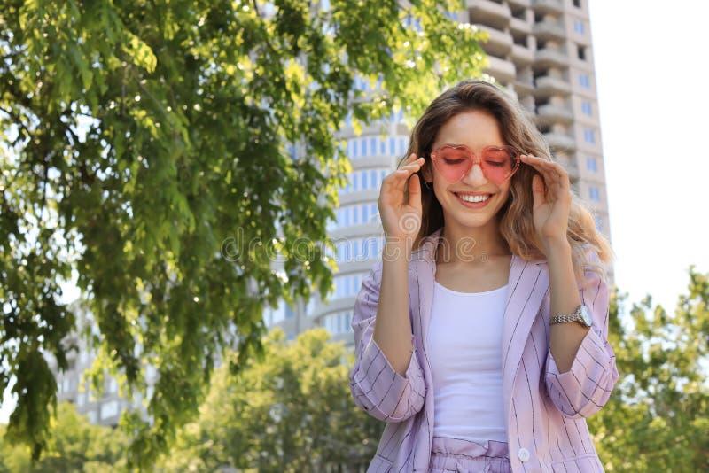 Il ritratto della giovane donna felice con cuore ha modellato i vetri in città il giorno soleggiato fotografia stock libera da diritti