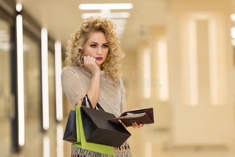 Il ritratto della giovane donna infelice che guarda in suo portafoglio nel centro commerciale, speso troppo, non abbastanza conta immagine stock libera da diritti