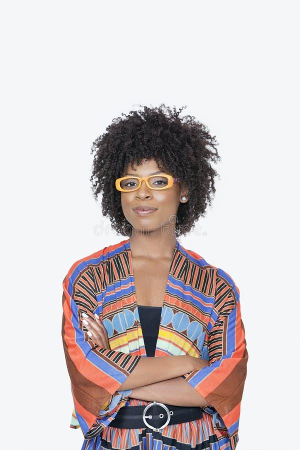 Il ritratto della giovane donna in mani diritte dell'abbigliamento africano della stampa ha ripiegato il fondo grigio fotografia stock