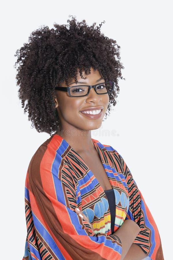 Il ritratto della giovane donna in mani diritte dell'abbigliamento africano della stampa ha ripiegato il fondo grigio immagini stock libere da diritti