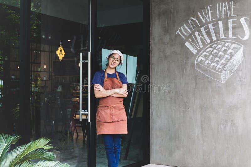 Il ritratto della giovane donna sorridente con le armi ha attraversato la condizione alla caffetteria fotografie stock libere da diritti