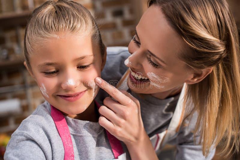 il ritratto della madre allegra che mette la farina sulle figlie affronta mentre fotografie stock