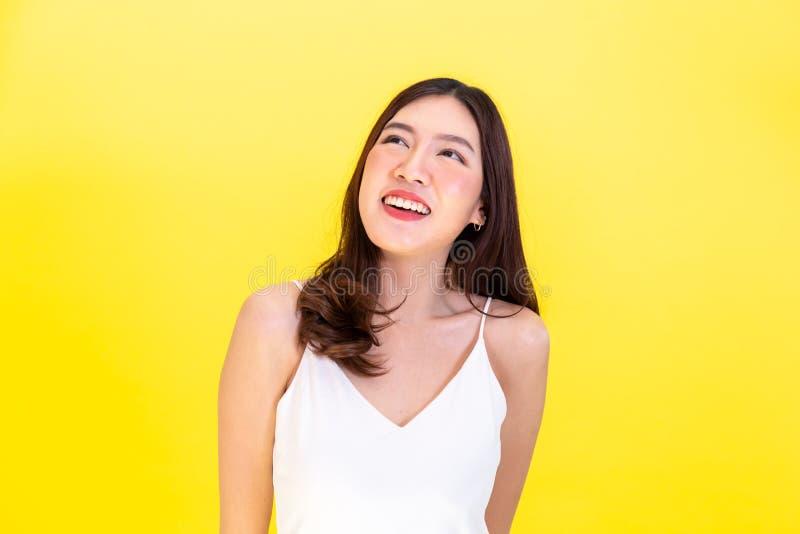 Il ritratto della mostra sorridente asiatica attraente della donna sveglia esprime fotografia stock libera da diritti
