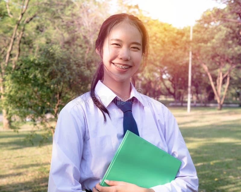 Il ritratto della ragazza allegra teenager uniforme dello studente tailandese della High School felice e rilassarsi tiene i libri immagini stock libere da diritti