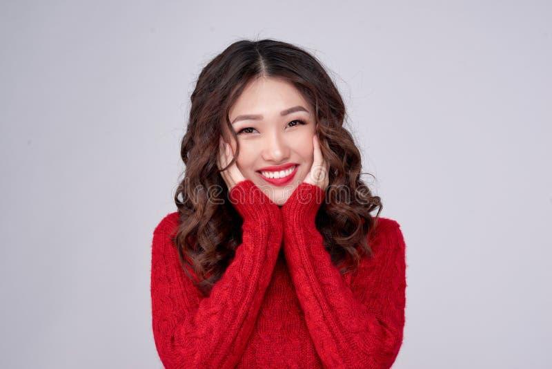 Il ritratto della ragazza asiatica dell'inverno di bellezza nel rosso ha tricottato il vestito di lana Festa di Natale fotografia stock
