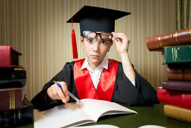 Il ritratto della ragazza astuta nella graduazione copre fare il compito immagine stock