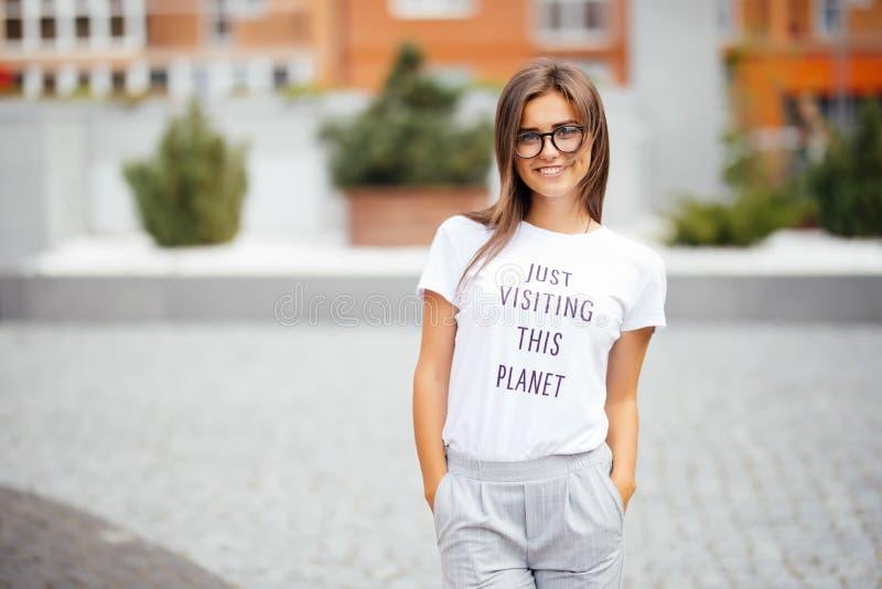Il ritratto della ragazza graziosa sveglia di sport con il sorriso felice, indossa i vetri dell'aviatore, espressione timida del  immagini stock