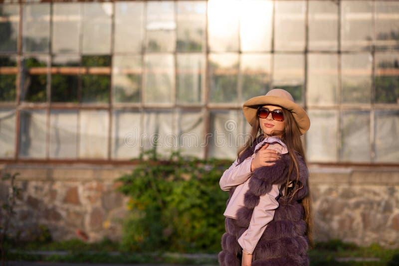 Il ritratto della via del modello castana alla moda indossa il cappello e gli occhiali da sole, godenti del tempo caldo Spazio vu immagine stock