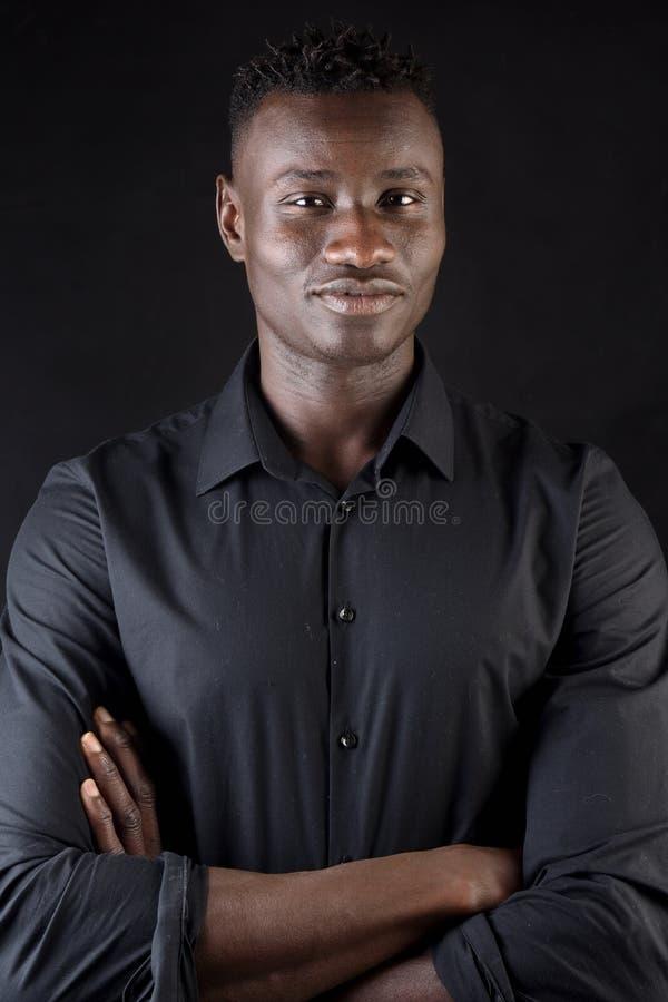 Il ritratto delle armi africane dell'uomo ha attraversato su fondo nero fotografia stock libera da diritti