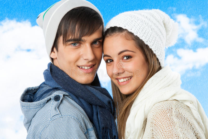 Il ritratto delle coppie teenager sveglie in inverno copre. immagini stock
