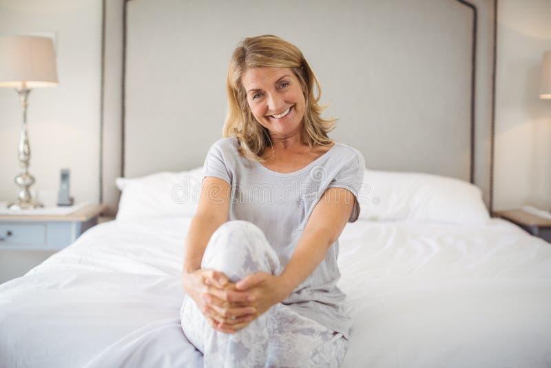 Il ritratto delle donne sorridenti che si siedono con le gambe ha attraversato sul letto - Gambe del letto ...