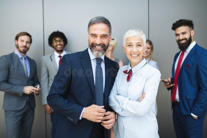 Il ritratto delle persone di affari che stanno con le armi ha attraversato in ufficio immagine stock
