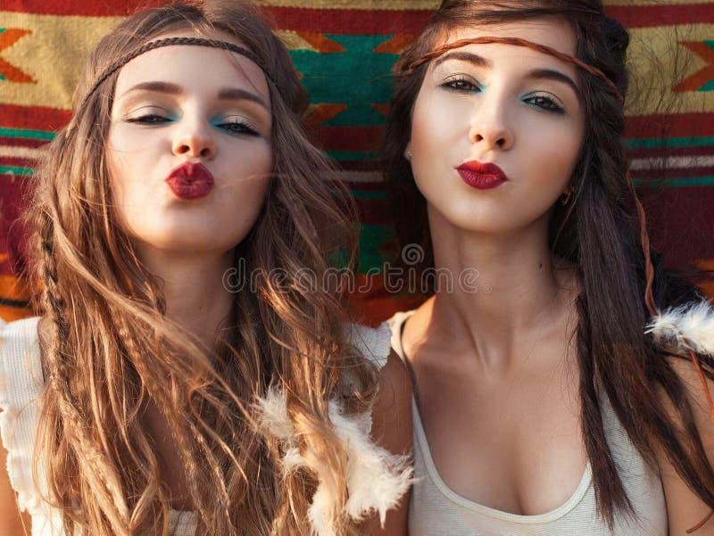 Il ritratto delle ragazze alla moda di hippy divertendosi ed invia il bacio sopra la e fotografie stock