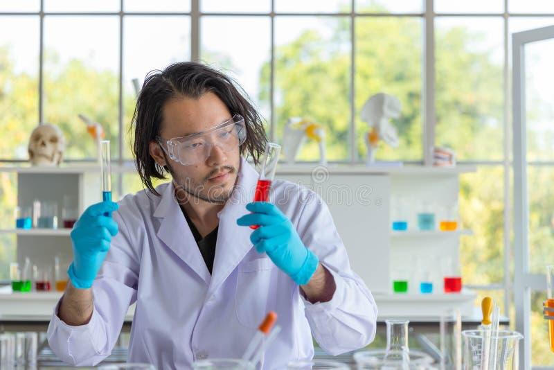 Il ritratto dello scienziato astuto asiatico dell'uomo sta tenendo due provette Nel laboratorio di ricerca fotografie stock libere da diritti
