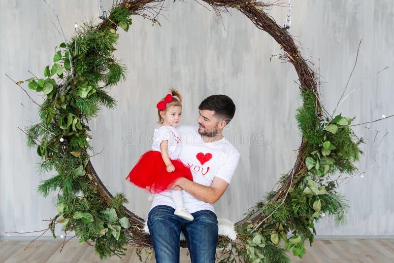 Il ritratto dello studio di una figlia del bambino e del padre su una corda oscilla St Giorno del ` s del biglietto di S immagini stock