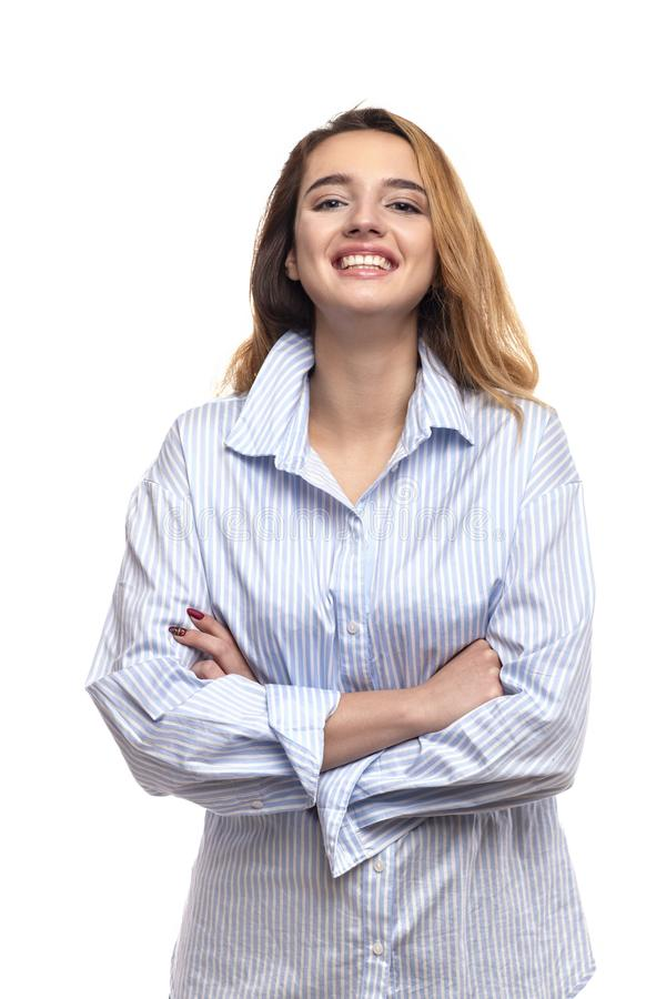 Il ritratto dello studio di una giovane donna con i jeans d'uso e la blusa dei capelli biondi lunghi con le armi ha attraversato, fotografia stock libera da diritti