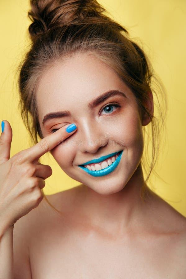 Il ritratto di arte di bellezza di giovane ragazza sorridente bianca in pastello tonifica il trucco blu del caramello Foto vertic immagine stock