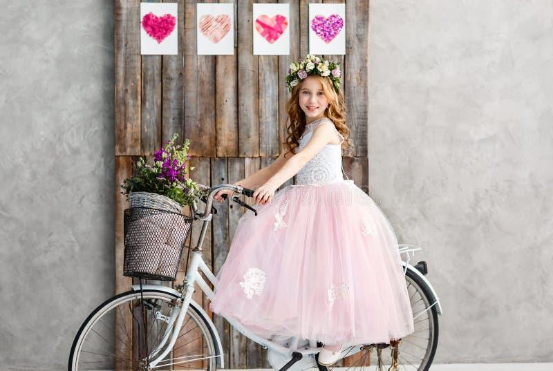 Il ritratto di bella bambina in una corona dei fiori freschi sulla sua testa si siede su una bici in un vestito rosa fertile Infa fotografie stock